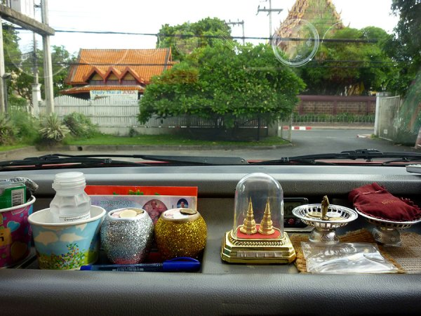 Red car taxi dashboard covered with good luck charms [Chiang Mai, Thailand, 2013]