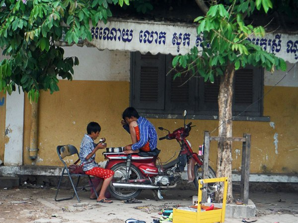 Siem Reap boys using motorbike seat as table