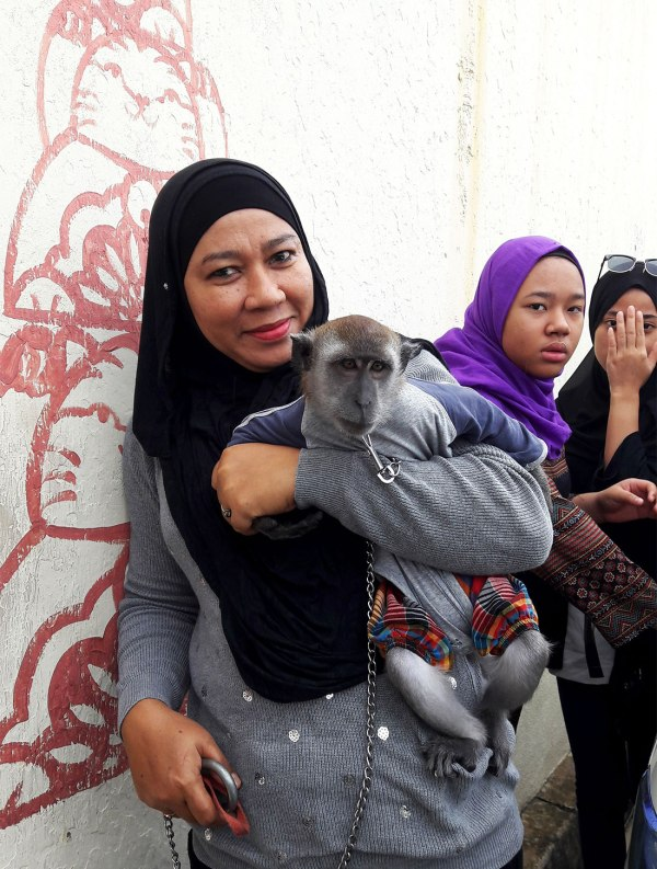 woman holding pet monkey in penang